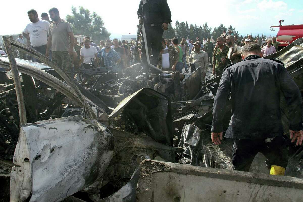 In this photo released by the Syrian official news agency SANA, Syrian security forces, emergency services and residents look at the remains of burned vehicles at the site of a bombing in Tartus, Syria, Monday, Sept. 5, 2016. Syrian state media reported that multiple bomb blasts have struck government and military targets around the country. (SANA via AP)
