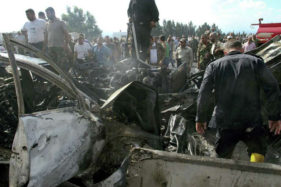 In this photo released by the Syrian official news agency SANA, Syrian security forces, emergency services and residents look at the remains of burned vehicles at the site of a bombing in Tartus, Syria, Monday, Sept. 5, 2016. Syrian state media reported that multiple bomb blasts have struck government and military targets around the country. (SANA via AP) Photo: AP / SANA