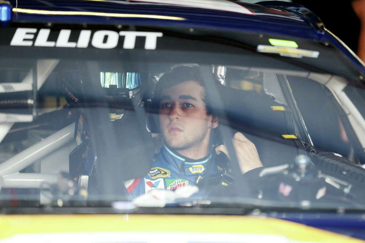 NASCAR driver Chase Elliott (24) adjusts his safety harness as he gets ready to practice for Sunday's race at Talladega Superspeedway.