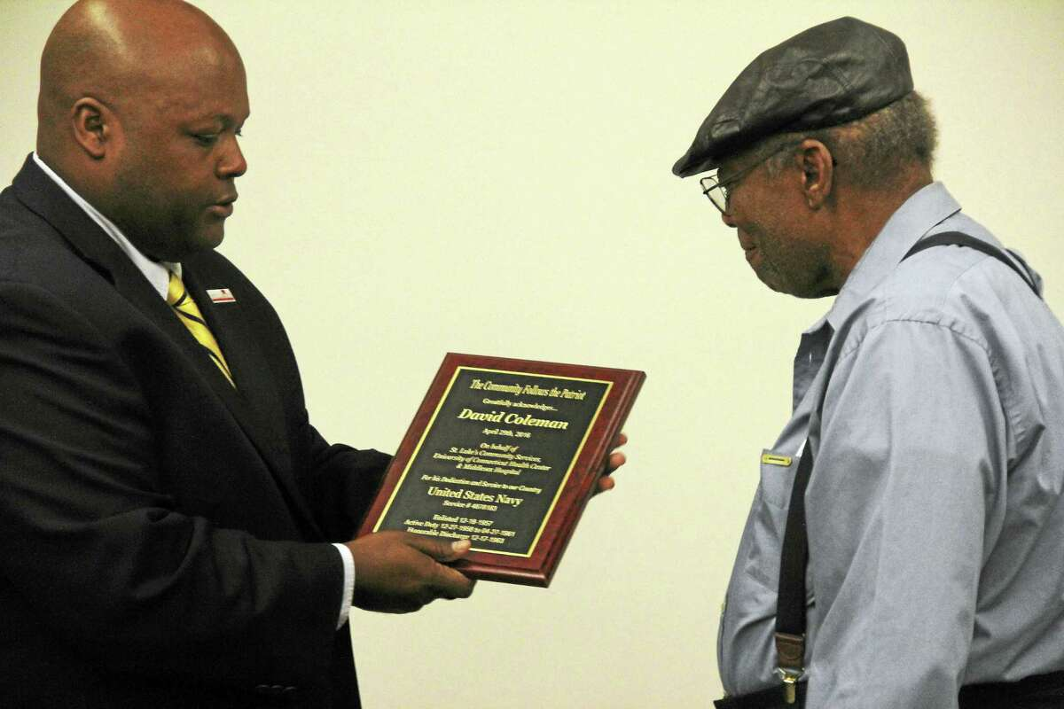Coleman receives The Community Follows the Patriot plaque Friday from Middletown Police Capt. Gary Wallace.
