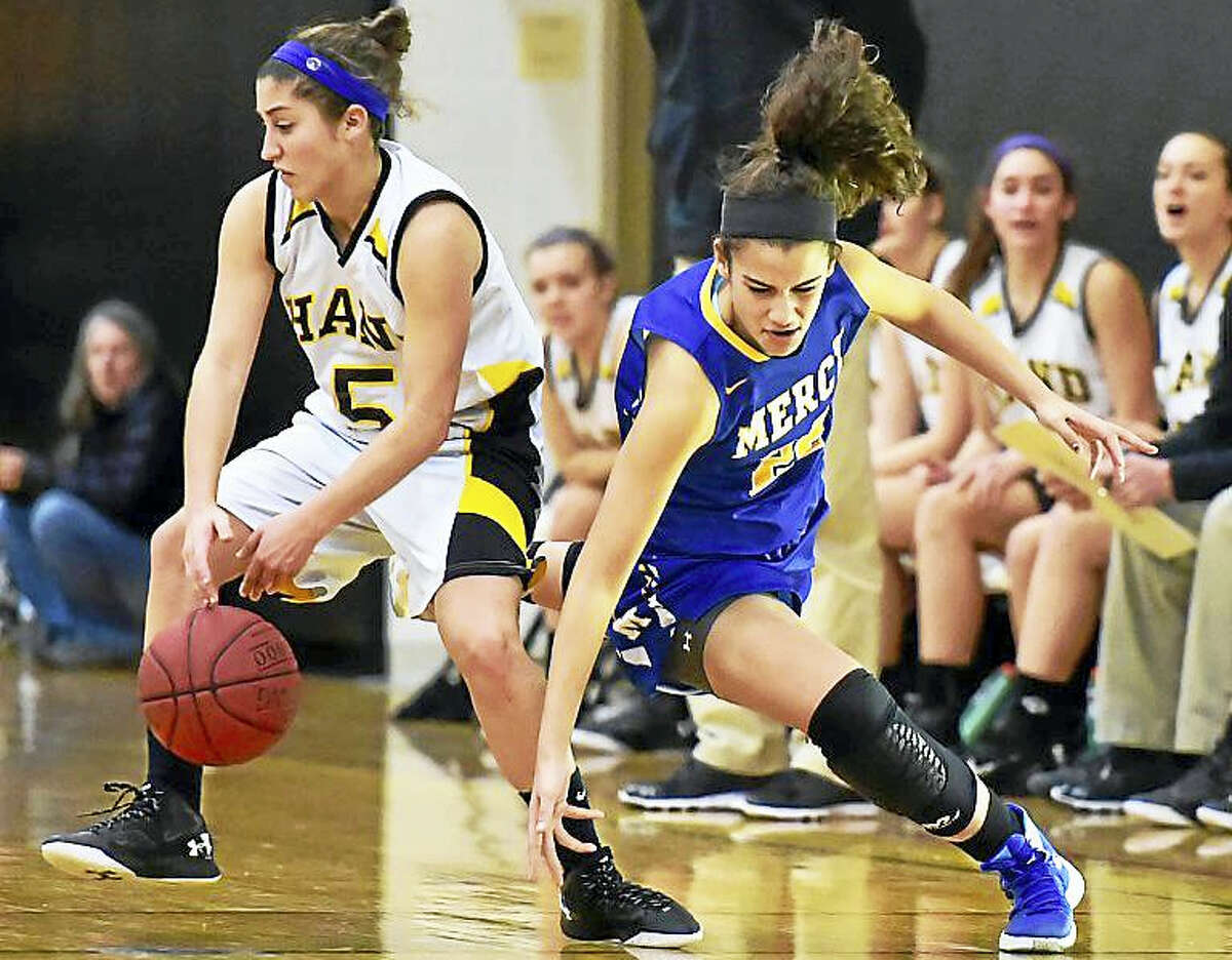 (Catherine Avalone – GameTime CT) Mercy junior Keri Kernisan attempts to steal back the ball from Hand's Gillian Draemer defends in a 77-56 win for the Mercy Tigers earlier this season in Madison.