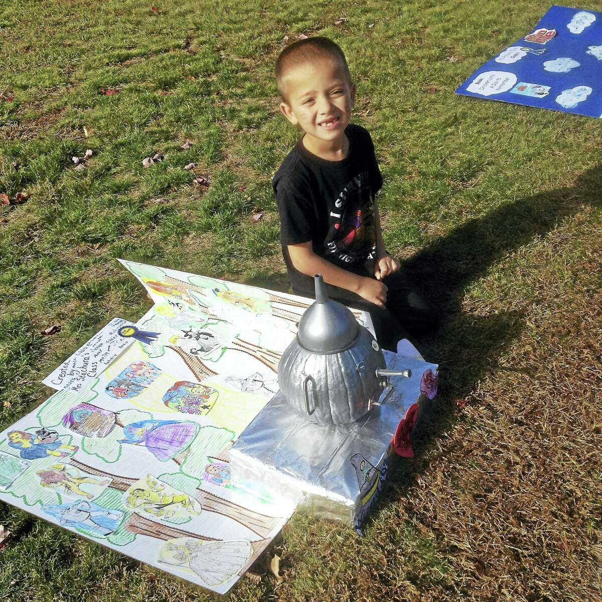 Edna C. Stevens Elementary School second-grader Dante sits with his brother Dario's class pumpkin, the Tin Man. The Halloween project, spearheaded by Cromwell teacher Karen Ambler, combined literacy with creativity.