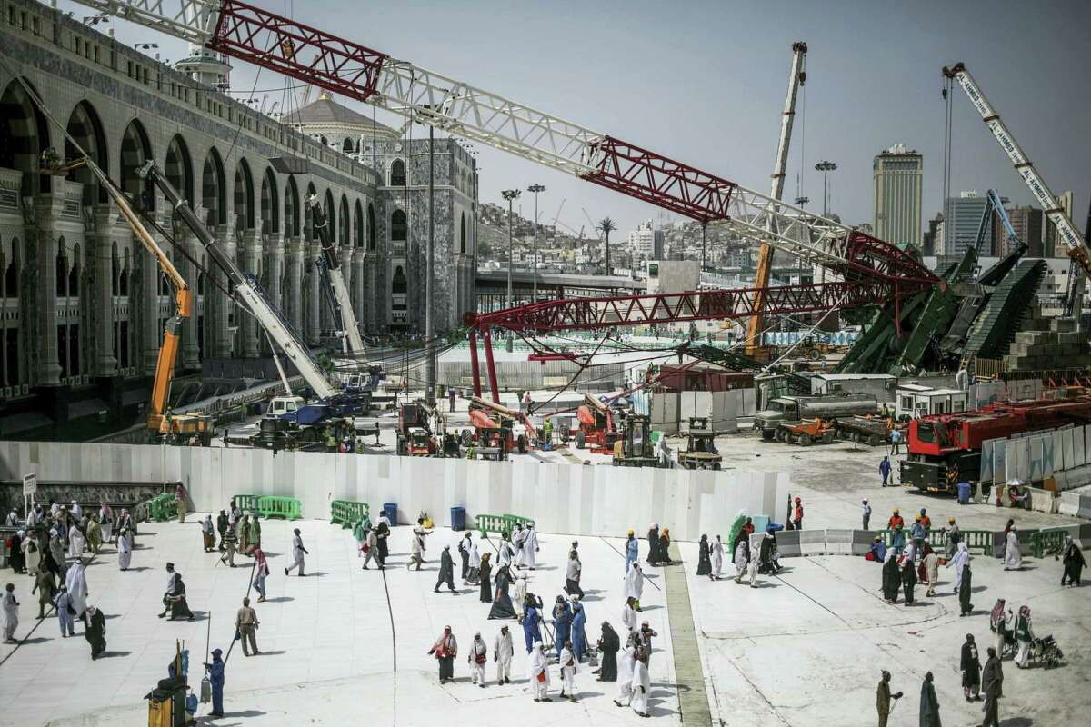 In this Tuesday, Sept. 15, 2015 photo, Muslim Pilgrims walk past the site of a crane collapse that killed over a hundred Friday at the Grand Mosque in the holy city of Mecca, Saudi Arabia. Employees at giant construction firm, the Saudi Binladin Group, have set fire to more than seven company buses to protest a reportedly large round of looming layoffs and not being paid their salaries for months.