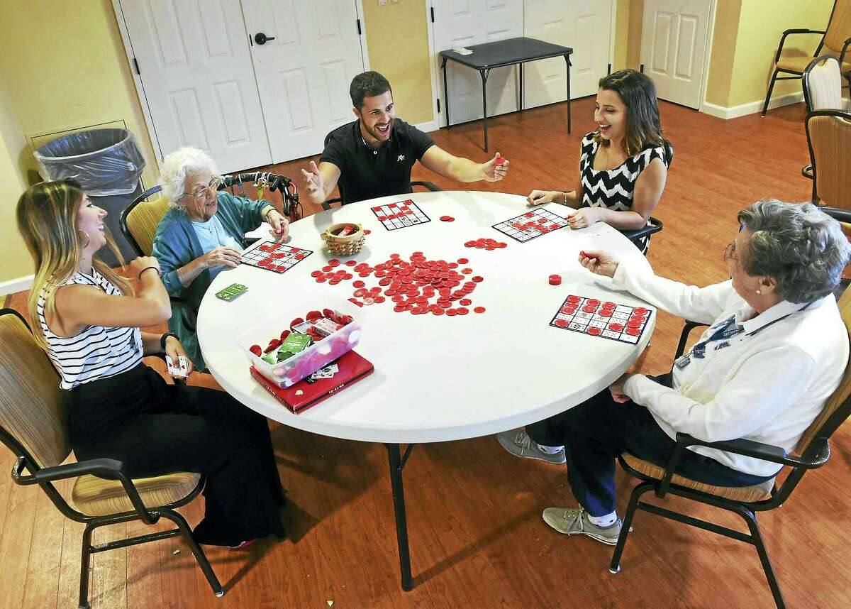 Quinnipiac University occupational therapy graduate student Joseph Huberman, 24, third from left, relishes his victory playing Pokeno with Quinnipiac University senior Victoria Kozar, 21, a health science major, fourth from left, as they interact with Mary Addario, second from left, and Eleanor Ruot far right, both residents of the Masonicare Ashlar Village Assisted Living Community in Wallingford, and Ashlar Village Recreation Coordinator Marisa Dominello.