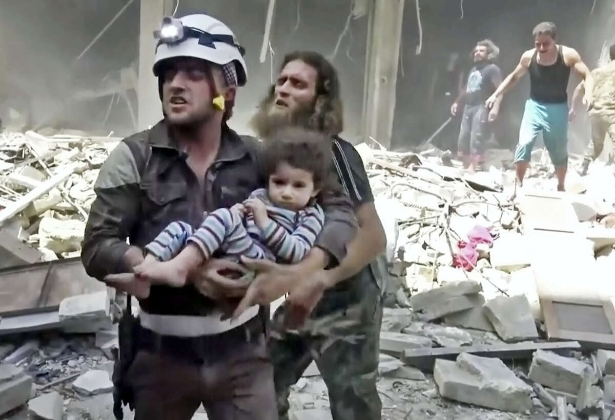 In this image made from video and posted online from Validated UGC, a Civil Defense worker carries a child after airstrikes hit Aleppo, Syria, Thursday, April 28, 2016. A Syrian monitoring group and a first-responders team say new airstrikes on the rebel-held part of the contested city of Aleppo have killed over a dozen people and brought down at least one residential building. The new violence on Thursday brings the death toll in the past 24-hours in the deeply divided city to at least 61 killed.