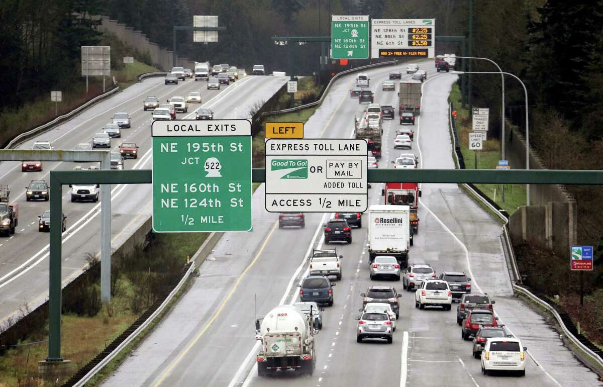 Signs on southbound Interstate 405 give information on the tolls for using express lanes Tuesday, Feb. 16, 2016, in Bothell, Wash. Gov. Jay Inslee announced plans Tuesday to try to decrease congestion on Interstate 405 in answer to commuter complaints that the new express lane tolling system is making traffic worse.
