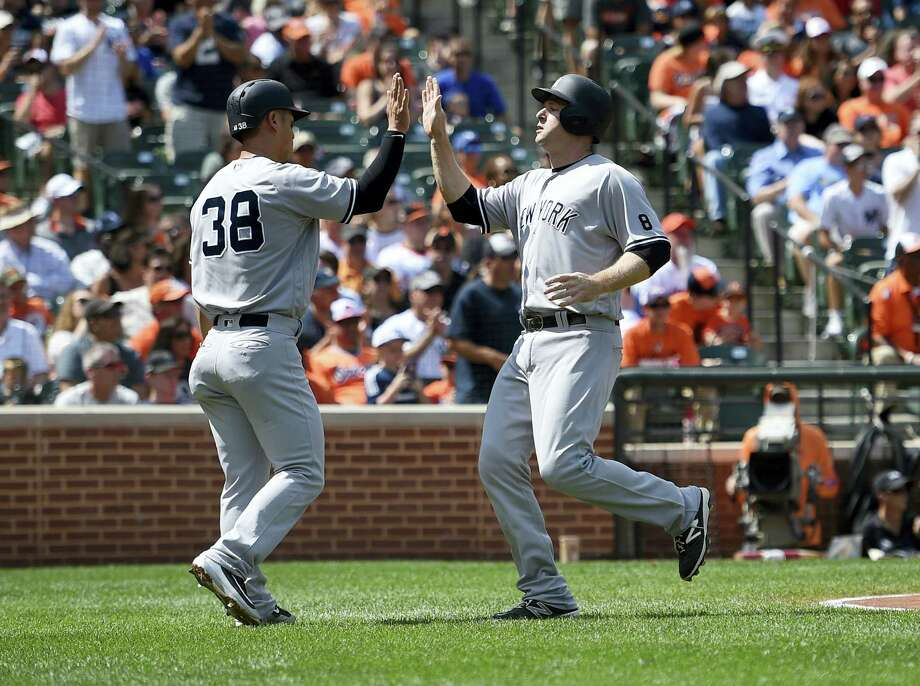 Rob Refsnyder, left, high-fives Chase Headley they scored on a single by Austin Romine in the first inning on Sunday. Photo: Nick Wass — The Associated Press  / FR67404 AP