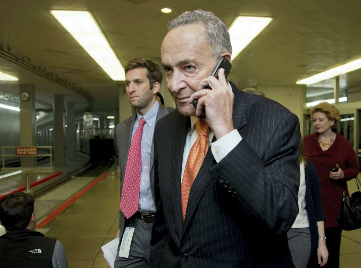 Sen. Chuck Schumer, D-N.Y., talks on a phone as he walks from the Senate subway on Capitol in Washington on Dec. 12, 2014.