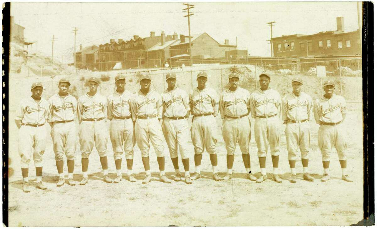 This 1928 photo provided by Christie's from their upcoming baseball memorabilia auction shows legendary Negro Leagues slugger Josh Gibson, fifth from the left, when he was a 16-year-old player with the Pittsburgh Crawfords semi-pro baseball team. A trove of nearly 500 baseball artifacts, the value of which could top $5 million, will be auctioned off by Christie's in New York on Oct. 19 and 20, 2016.
