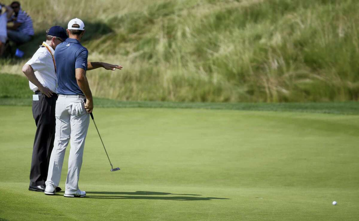 In this June 19, 2016 photo, Dustin Johnson, right, talks to a rules official on the fifth green during the final round of the U.S. Open golf tournament at Oakmont Country Club in Oakmont, Pa. Top rules experts from around the world have been meeting privately the last five years to simplify the rules in what could be the most expansive rules overhaul ever.