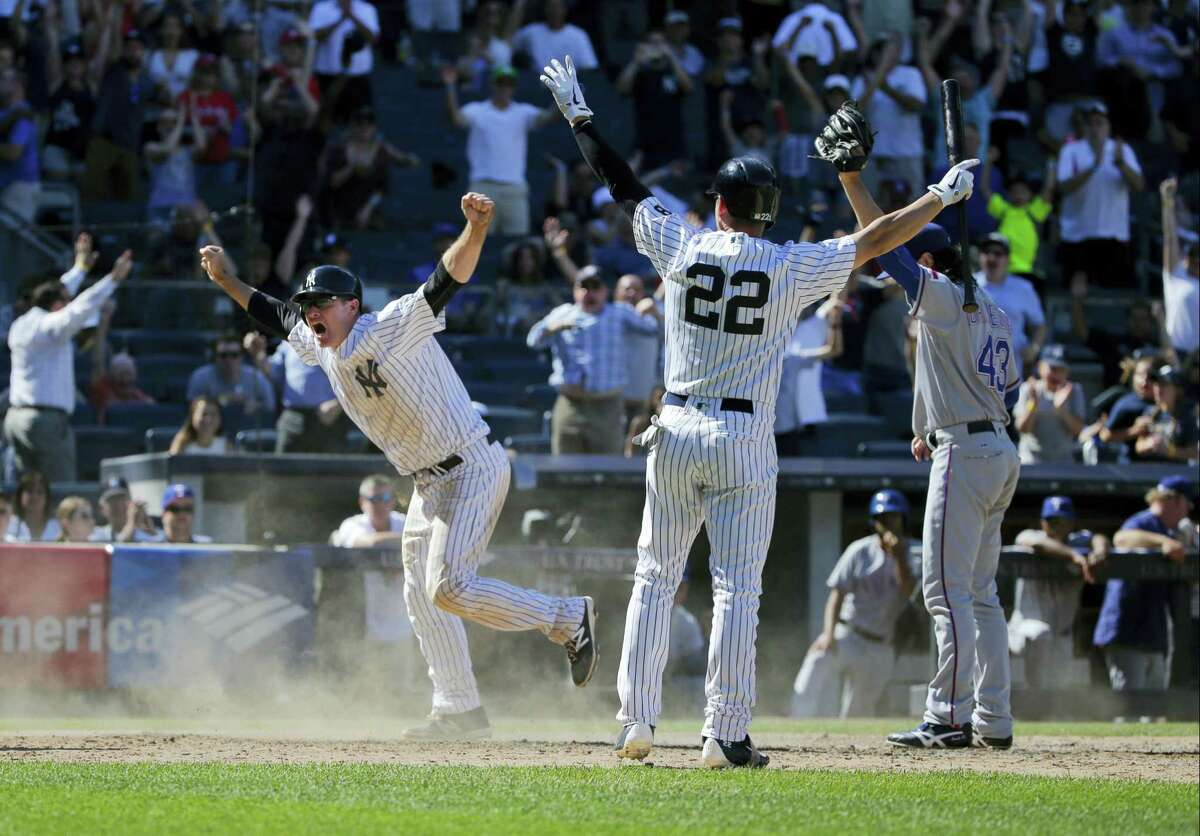 Jacoby Ellsbury (22) celebrates after Chase Headley, left, slid safely into home to score the game winning-run on Thursday.