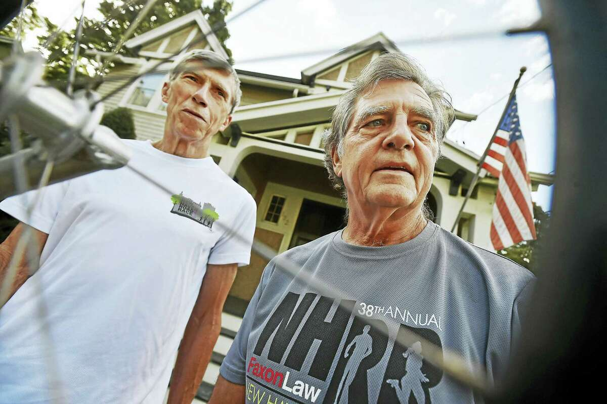 Bill Schaeffer, left, and Peter Halsey, photographed Tuesday, August 30, 2016, outside Halsey's home in New Haven. They are two of 12 runners who have participated every year in the Faxon Law New Haven 20K Road Race. The race, in its 39th year, is on Labor Day, September 5. They are seen through the spokes of a racing wheelchair Halsey used during two of the races when he was injured and could not run.