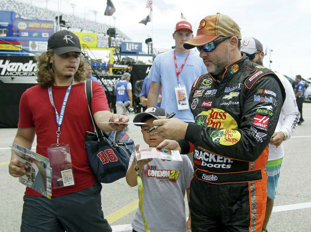 Tony Stewart, right, signs autographs during practice at Daytona International Speedway on Thursday.