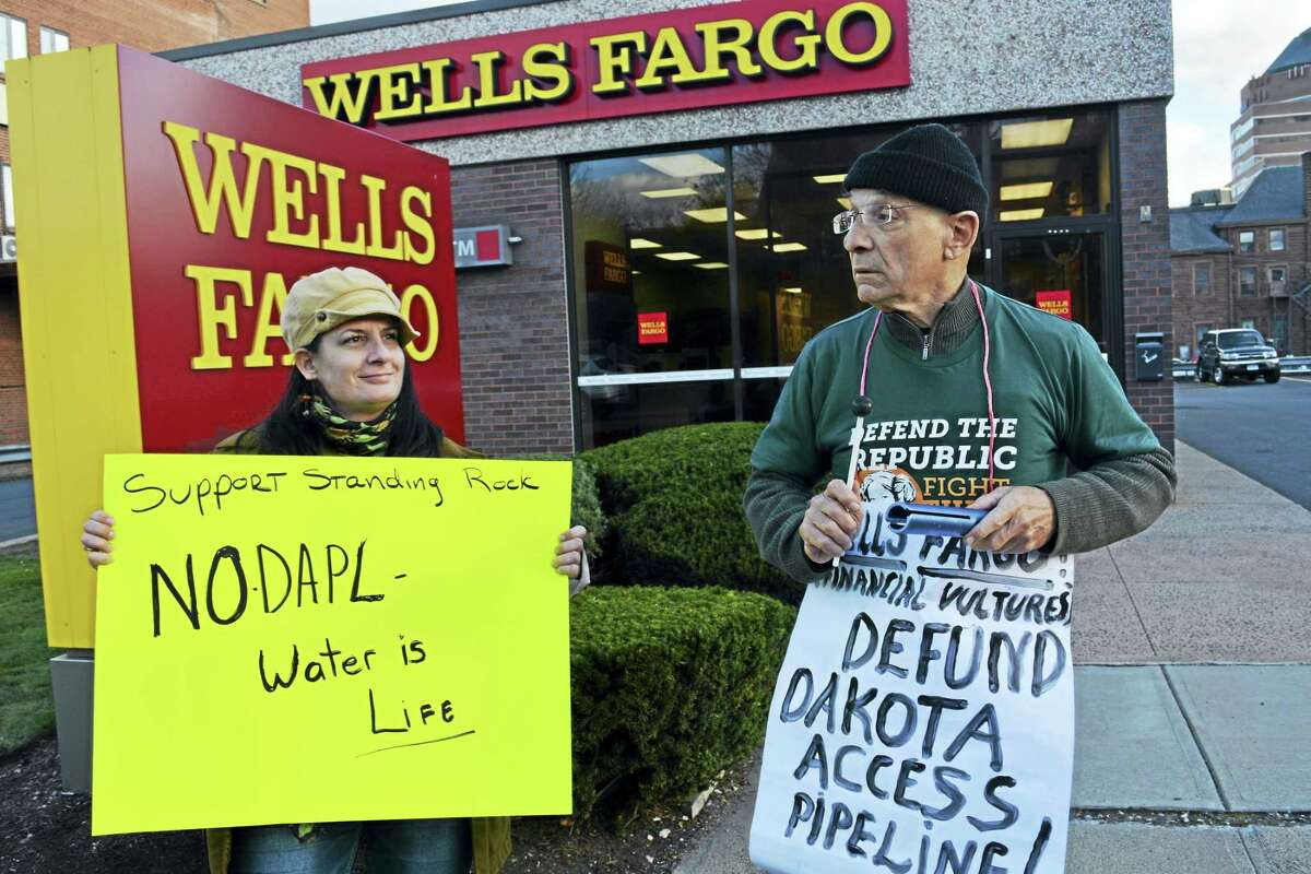 About eight activists, including Kathryn Mancarella of New Britain and Vic Lancia of Middletown, stand outside the Wells Fargo Bank on Washington Street in Middletown, protesting the Dakota Access Pipeline.