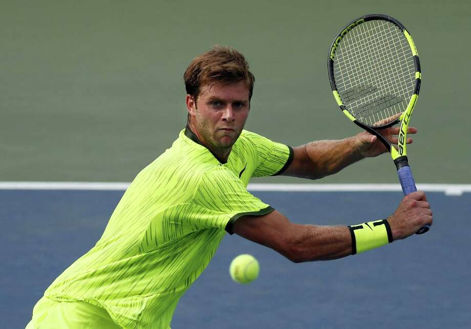 Ryan Harrison of the United States returns a shot to Milos Raonic of Canada during the second round of the U.S. Open tennis tournament Wednesday. Harrison upset the fifth-ranked Raonic in four sets. Photo: ALEX BRANDON — THE ASSOCIATED PRESS  / Copyright 2016 The Associated Press. All rights reserved.
