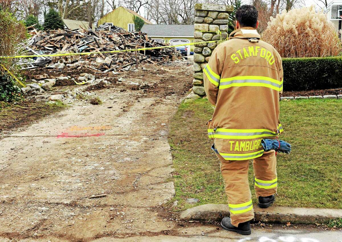 Stamford firefighter Nick Tamburro pays his respects outside the home of Madonna Badger in Stamford in 2011.