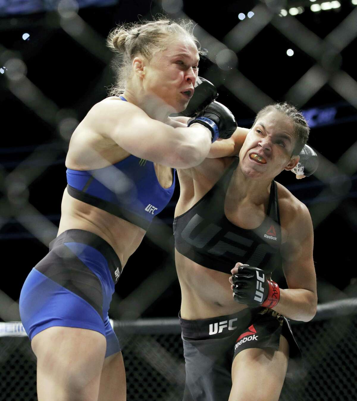 Amanda Nunes, right, connects with Ronda Rousey during the first round of their bout at UFC 207 Friday in Las Vegas.