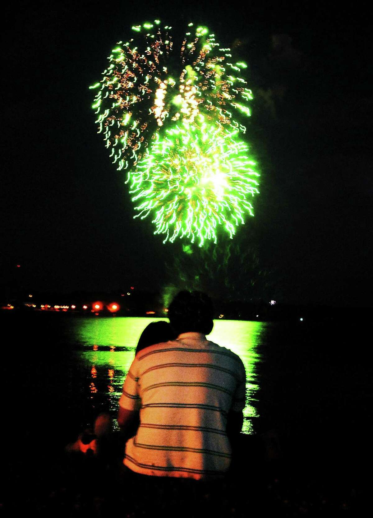 A father and daughter watch the July 4th fireworks.