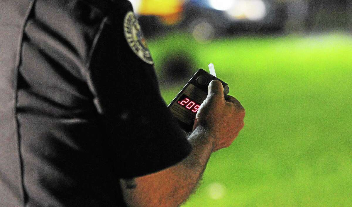 A police officer reads a breath testing device during a sobriety check.
