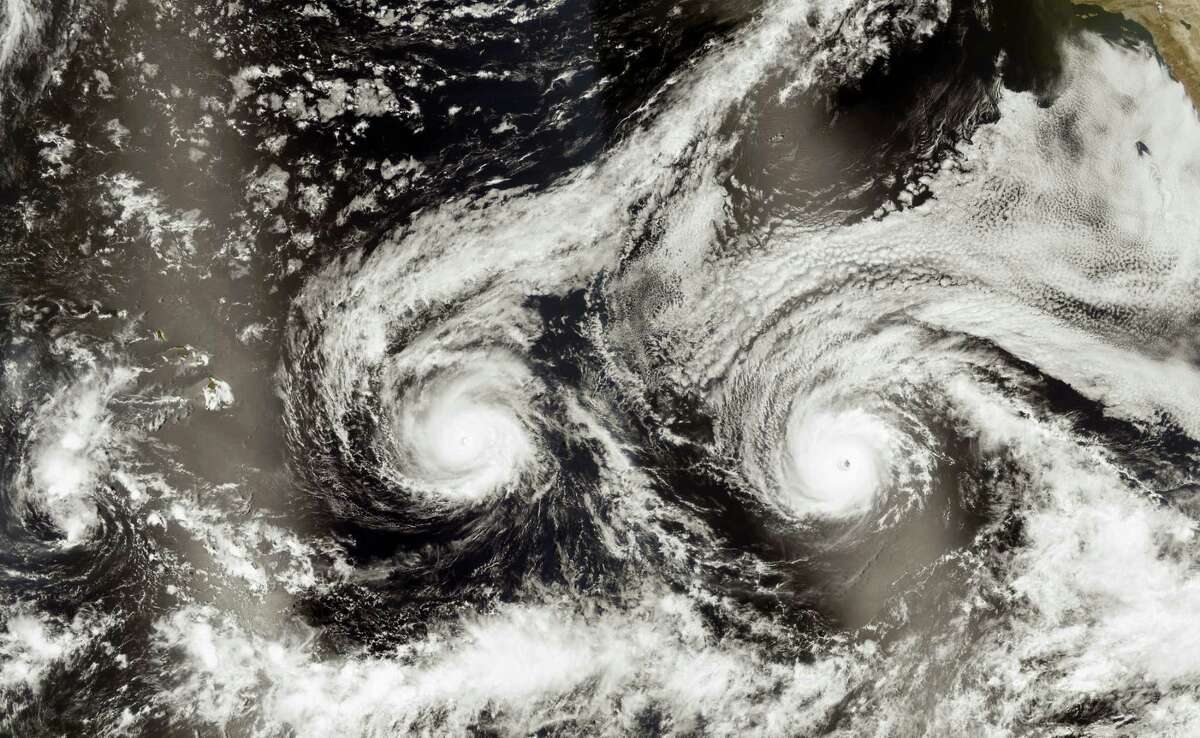 This satellite image taken Monday, Aug. 29, 2016, and released by NASA shows Hurricane Madeline, left, and Hurricane Lester over the Pacific Ocean in a composite built from two overpasses by the Visible Infrared Imaging Radiometer Suite on the Suomi NPP satellite. The National Weather Service issued a hurricane warning as the storm dubbed Madeline churned west Tuesday, Aug. 30, 2016, toward the island, urging residents to rush through preparations to protect themselves and their property and expect hurricane conditions within the next 36 hours.