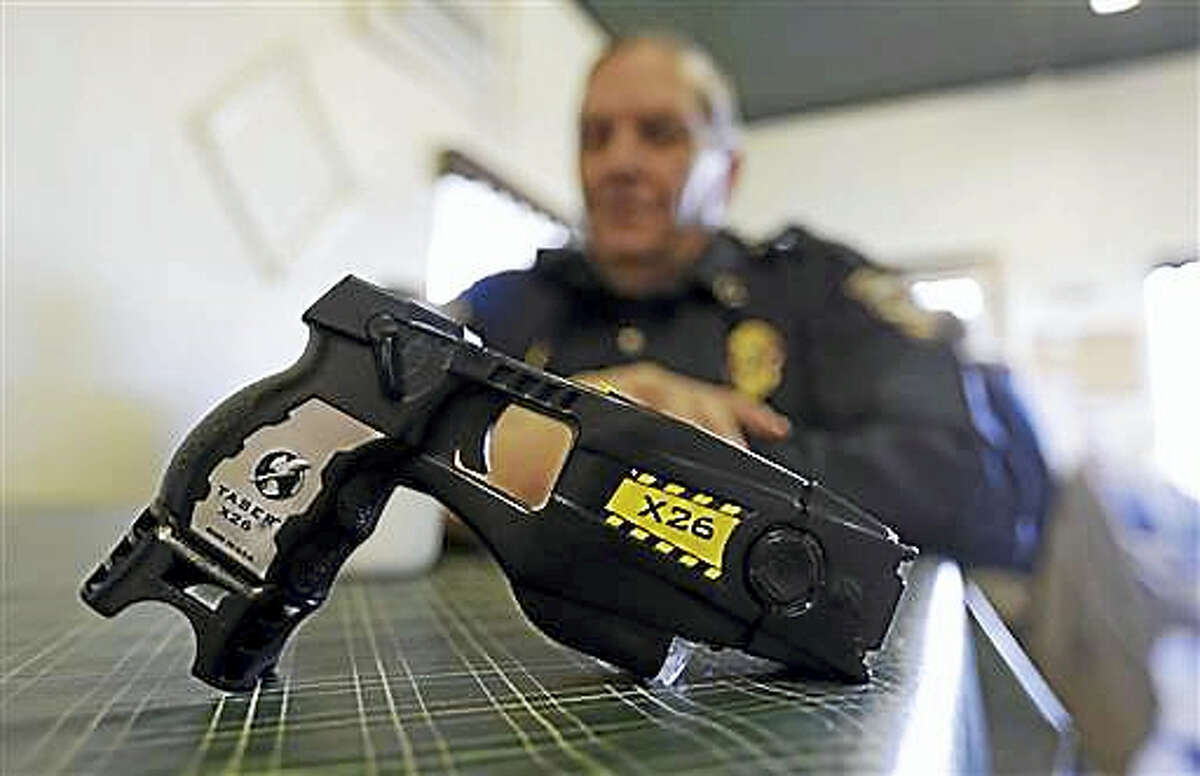 In this Nov. 14, 2013, file photo, a Taser X26 sits on a table in Knightstown, Ind. In Connecticut, a new report suggests police are more likely to use stun guns on minorities. Central Connecticut State University released its analysis Thursday, June 30, 2016, of the first statewide data of police stun gun use in the United States.