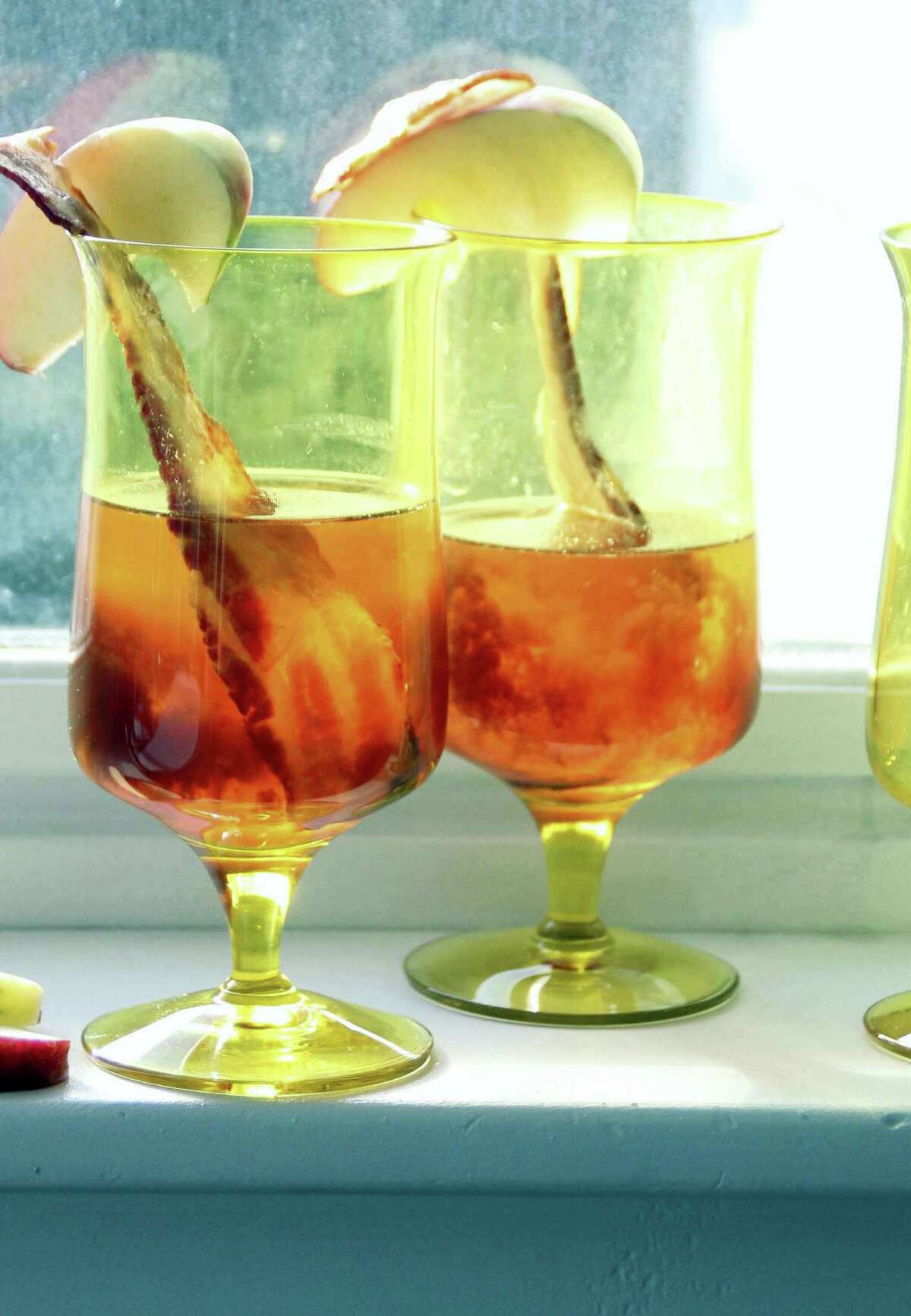 The Muppets Make Manhattans is made with apple brandy and sweet vermouth, with an apple slice and bacon garnish.