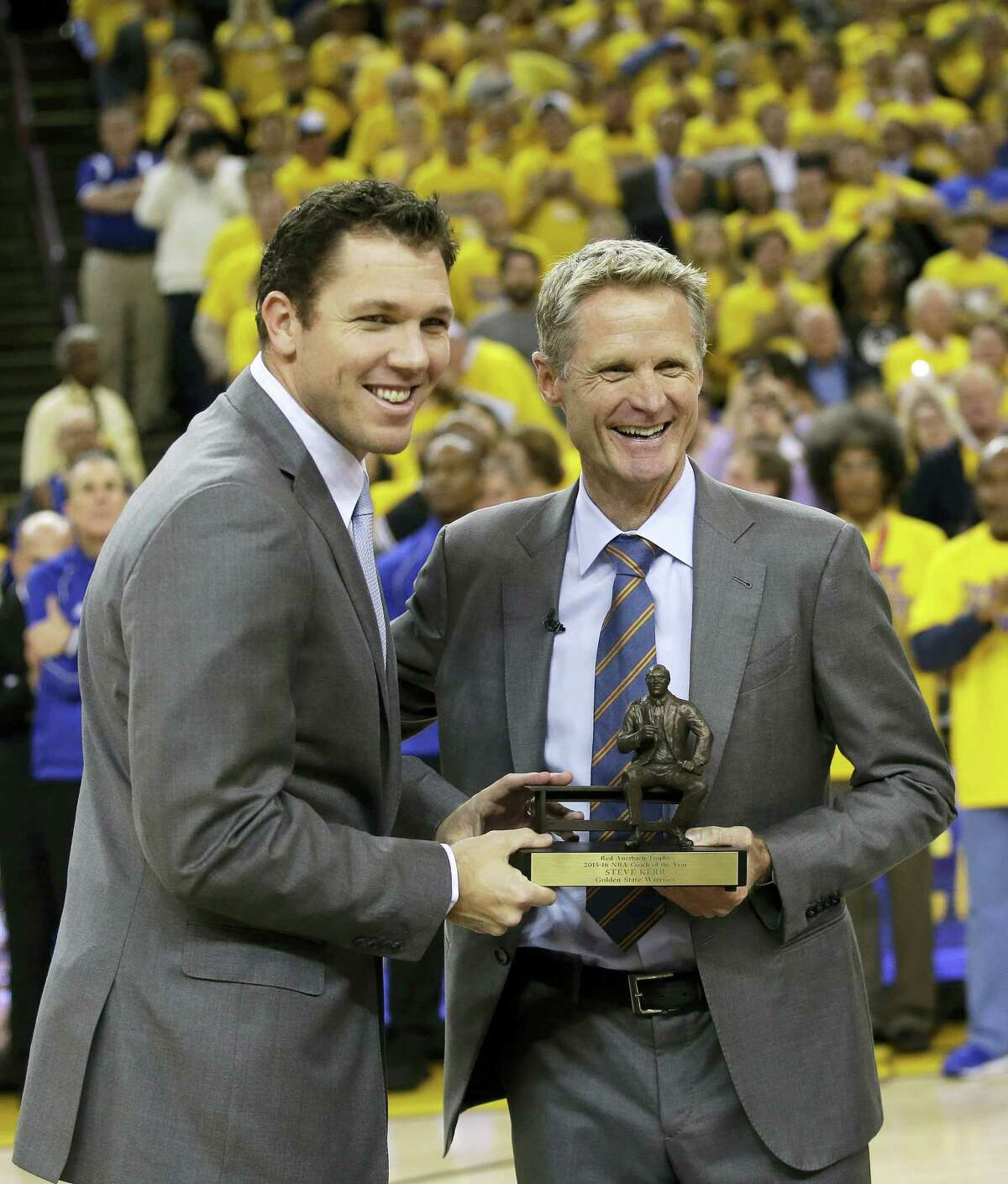 Golden State Warriors head coach Steve Kerr, right, poses for a photo with the league's coach of the year trophy alongside assistant coach Luke Walton.