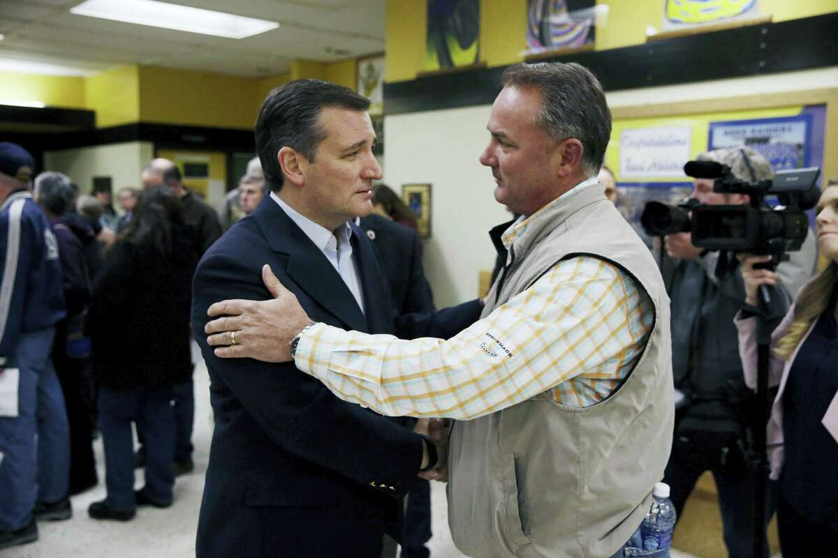 Republican presidential candidate, Sen. Ted Cruz, R-Texas, center left, talks with voter Greg Gerhardt while visiting a caucus location Tuesday, Feb. 23, 2016, in Reno, Nev.