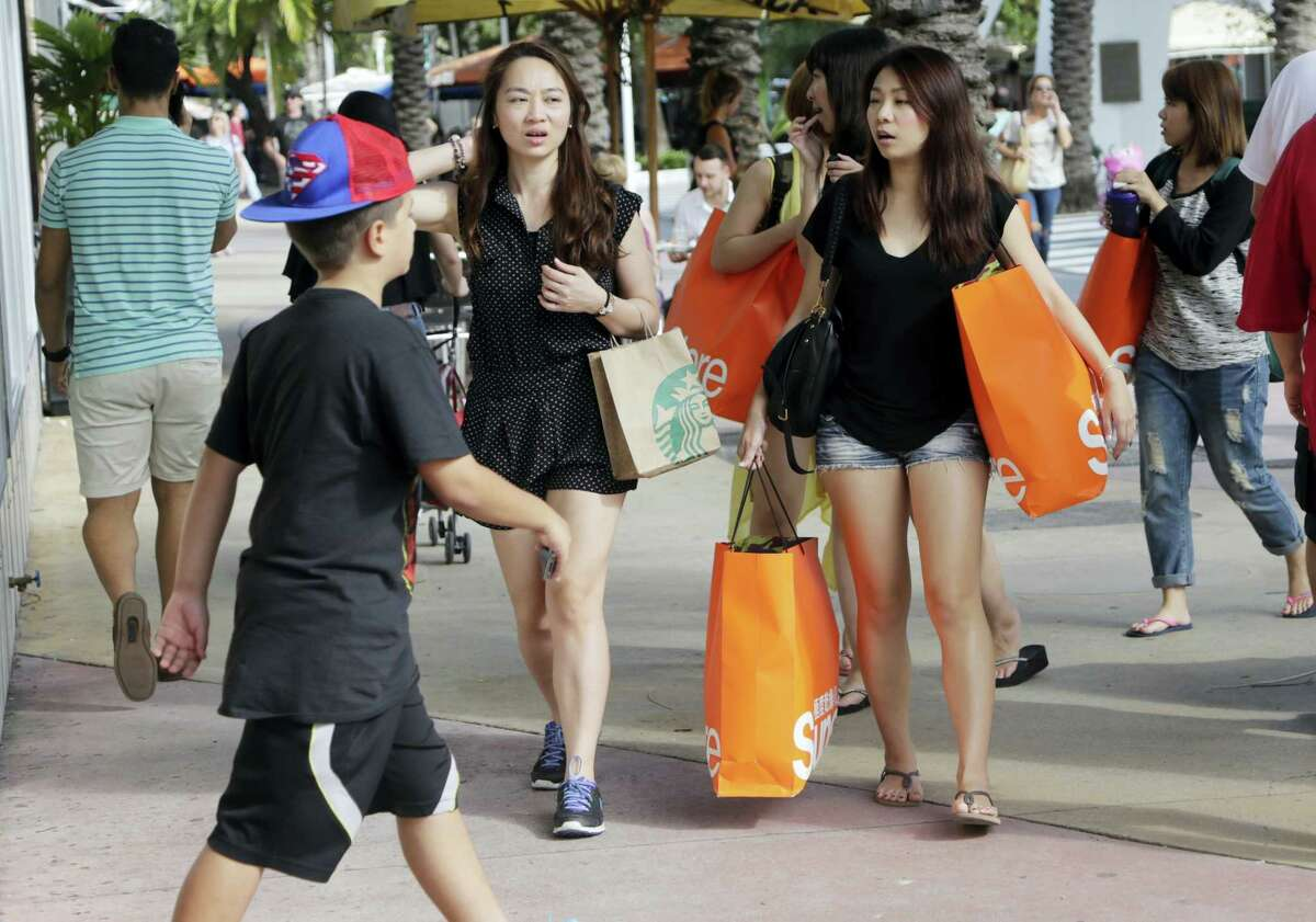 In this Feb. 3, 2016, photo, tourists from Taiwan carry shopping bags as they walk along Lincoln Road Mall, a pedestrian area featuring retail shops and restaurants in Miami Beach, Fla. The Conference Board releases its February index on U.S. consumer confidence on Feb. 23, 2016.