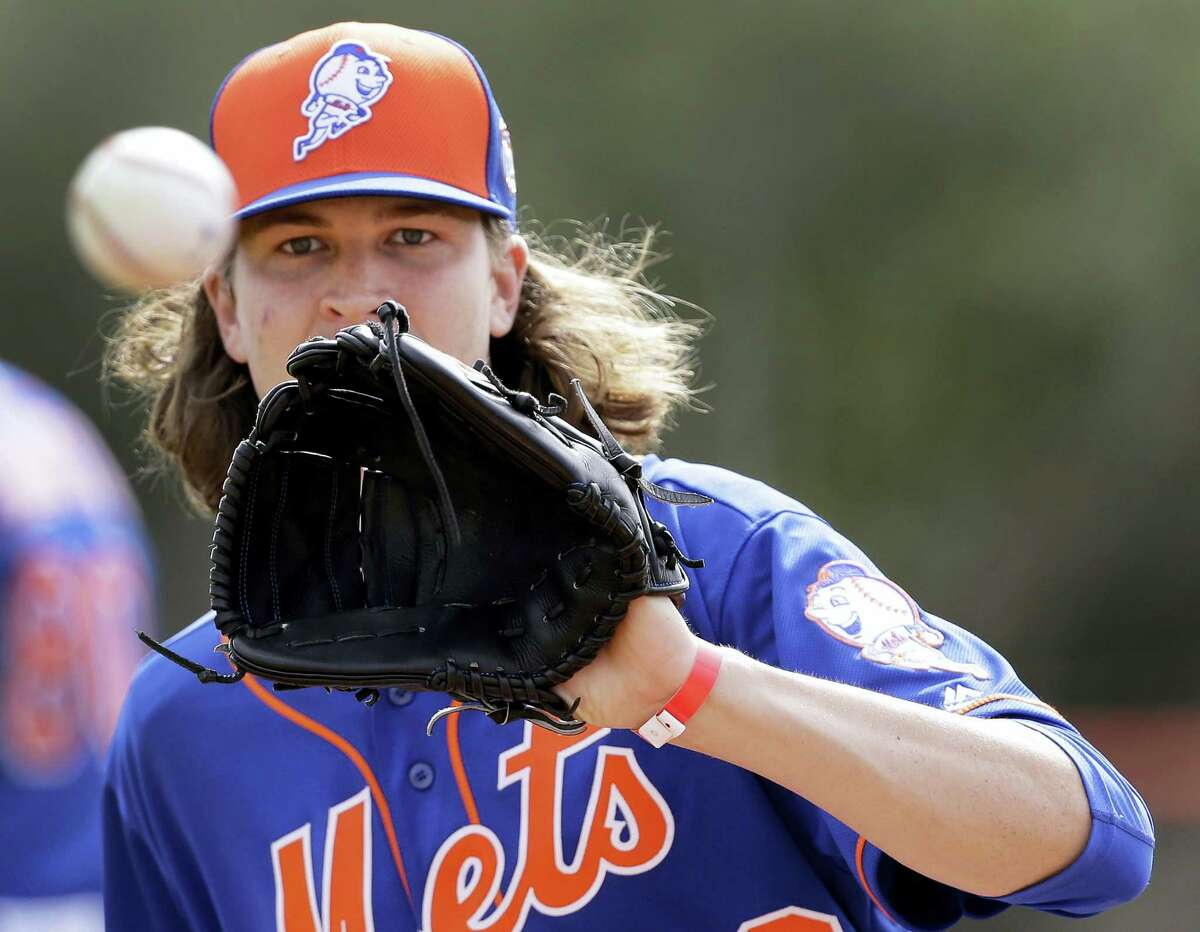 New York Mets pitcher Jacob deGrom catches a ball during spring training baseball practice Saturday, Feb. 20, 2016, in Port St. Lucie, Fla. (AP Photo/Jeff Roberson)