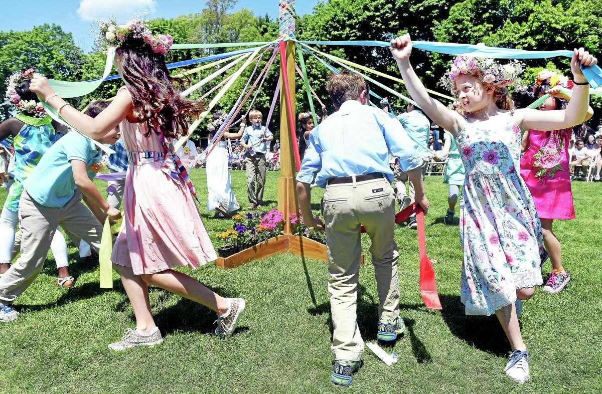 Schoolchildren dance around the maypole during a May Day celebration.