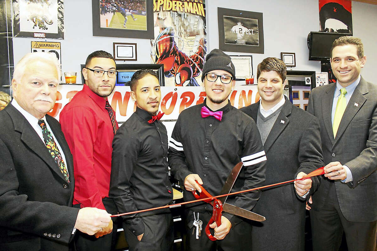 Ernesto Vargas (center with scissors) recently opened Finesse Cuts Barbershop on Main Street in Middletown. He was a participant in the chamber's Middletown Summer Youth Employment Program in 2008 and his host worksite was a barbershop. The grand opening on Dec. 14 drew members of his team and Middletown Small Business Development Center Counselor Paul Dodge, far left, chamber Vice President Jeff Pugliese, far right, and Middletown Mayor Dan Drew, second from right.