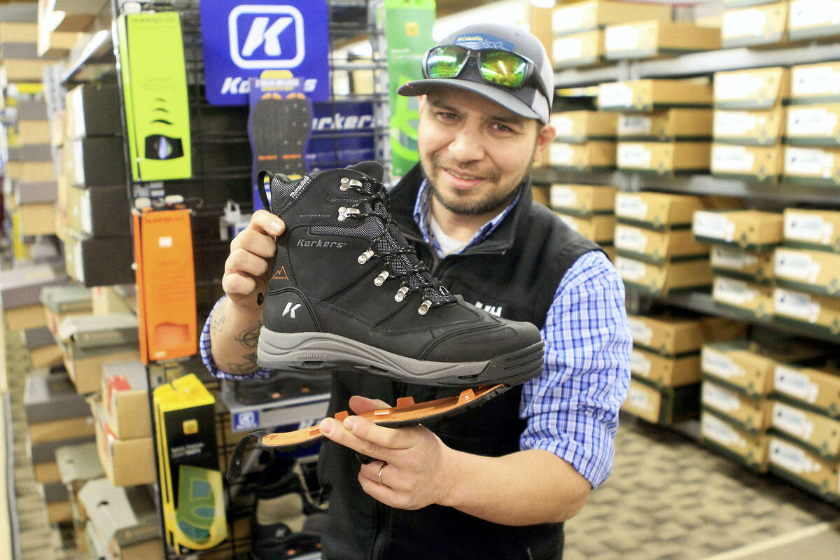 Stewart Valladolid, boot buyer at B&J Sporting Goods, demonstrates a boot by Korkers featuring interchangeable outer soles with and without studs in Anchorage, Alaska.