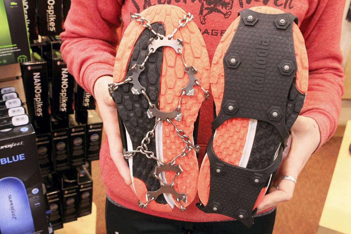 Emma Bohman, a sales associate at Skinny Raven sporting goods, shows two kinds of exterior cleats attached to running shoes in Anchorage, Alaska.