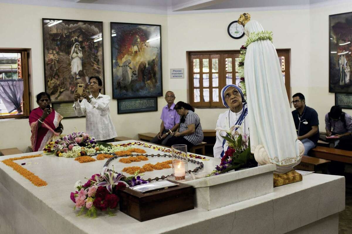 Worshippers gather around the tomb of Mother Teresa inside the Mother house in Kolkata, India, Saturday, Sept. 3, 2016. For many of the poor and destitute whom Mother Teresa served, the tiny nun was a living saint. Many at the Vatican would agree, but the Catholic Church nevertheless has a grueling process to make it official, involving volumes of historical research, the hunt for miracles and teams of experts to weigh the evidence. In Mother Teresa's case, the process will come to a formal end Sunday when Pope Francis declares the church's newest saint.