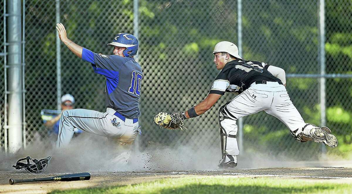 CATHERINE AVALONE — THE MIDDLETOWN PRESS East Haddam's Zach Lawrence slides in at home scoring on a fielder's choice as catcher Madison's Matt Sampson reaches out for the tag in a 6-2 win for Post 156 Wednesday.