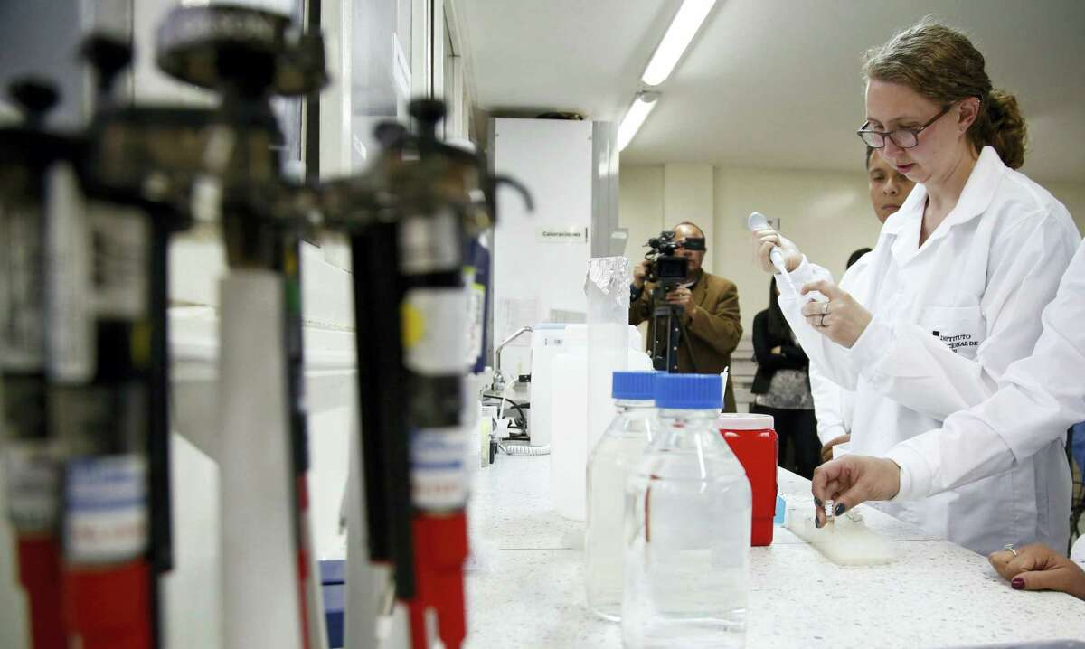 A Centers for Disease Control and Prevention, CDC, pathologist Brigid Bollweg works in Colombia's National Institute of Health in Bogota, Colombia, Tuesday, April 26, 2016. Margaret Honein, of the CDC, said during a press conference in Colombia that apart from microcephaly, babies whose mothers have had Zika during pregnancy may eventually acquire impaired hearing or vision.
