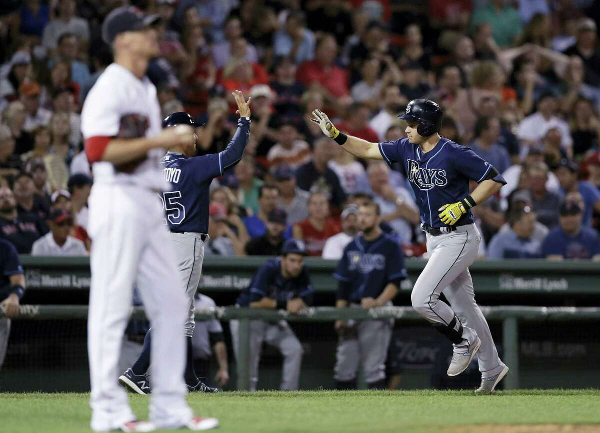 Tampa Bay's Evan Longoria, right, is congratulated by third base coach Charlie Montoyo after his solo home run off Boston Red Sox pitcher Clay Buchholz during the eighth inning at Fenway Park Tuesday. The Rays won 4-3.
