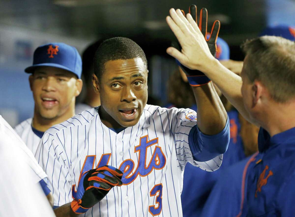 New York's Curtis Granderson is congratulated in the dugout after he hit a two-run home run during the seventh inning against the Miami Marlins, Tuesday. Relief pitcher Hansel Robles is at left. Granderson homered twice and the Mets won 7-4.