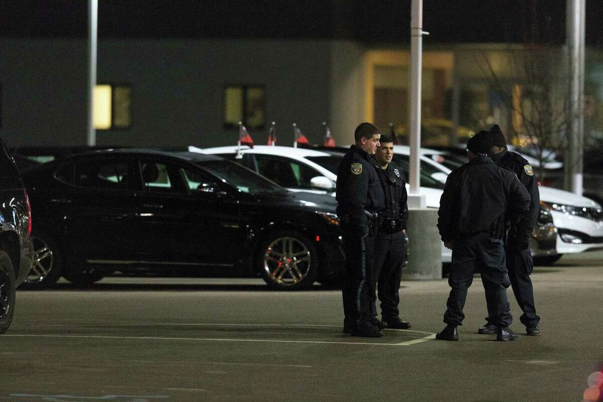 Police the area in the parking lot of a car dealership, after a random shooting on Feb. 21, 2016 in Kalamazoo.