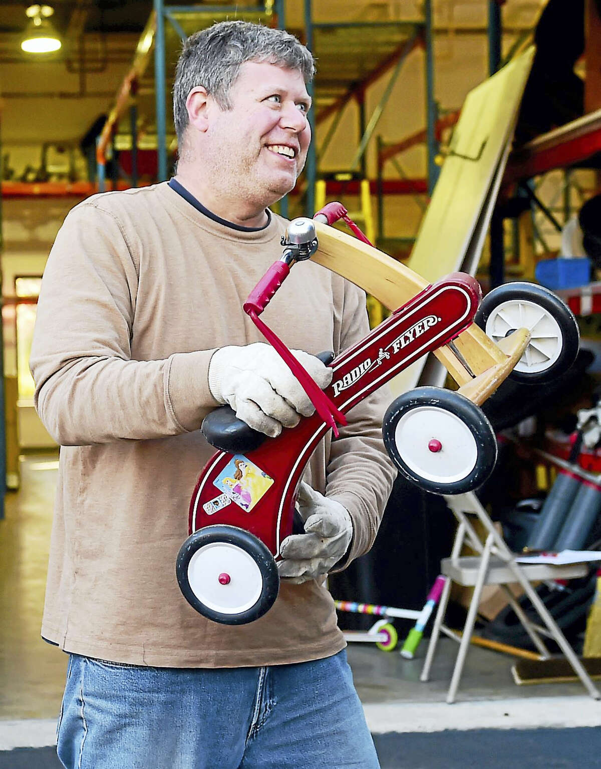 Volunteer Brian Lewis of Old Saybrook, left, helps Bikes For Kids move by loading a tricyle onto a Zanes Cycles delivery truck from the former Old Saybrook location.