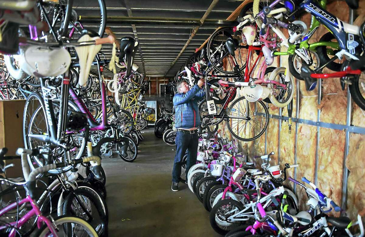 Tom Girard, Zanes Cycles of Branford retail manager in their Branford warehouse, works in the storage area for the Zanes Cycles trade-in program that benefits needy children. Zanes also donates bicycles to the Bike For Kids organization.