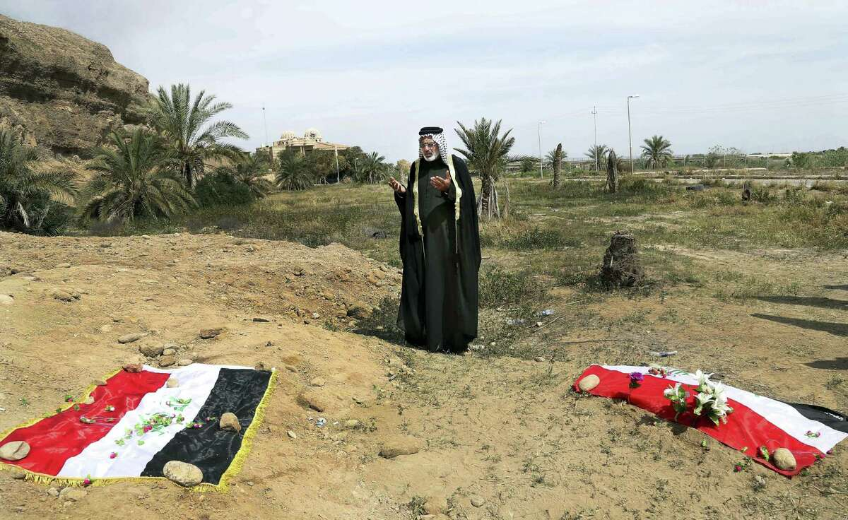 FILE - In this April 3, 2015, file photo, an Iraqi man prays for his slain relative at the site of a mass grave believed to contain the bodies of Iraqi soldiers killed by Islamic State group militants when they overran Camp Speicher military base in Tikrit, Iraq, in June 2014. An analysis by The Associated Press has found 72 mass graves left behind by Islamic State extremists in Iraq and Syria, and many more are expected to be discovered as the group loses territory. (AP Photo/Khalid Mohammed, File)