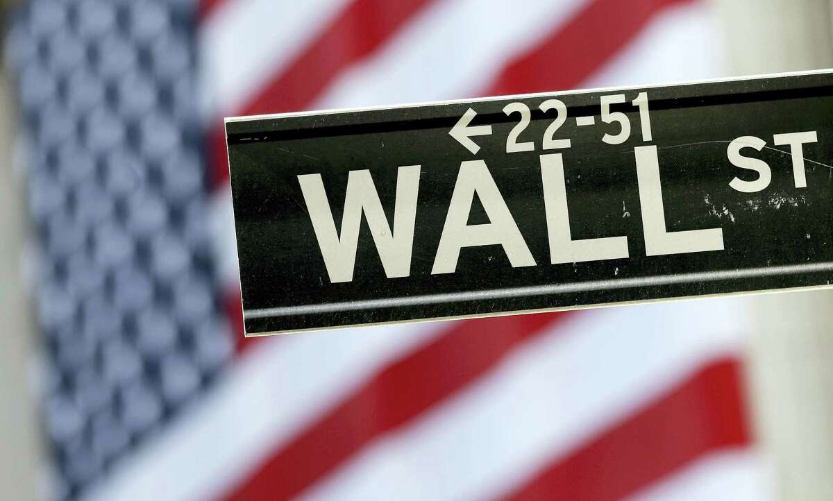 A Wall Street street sign is framed by an American flag hanging on the facade of the New York Stock Exchange.