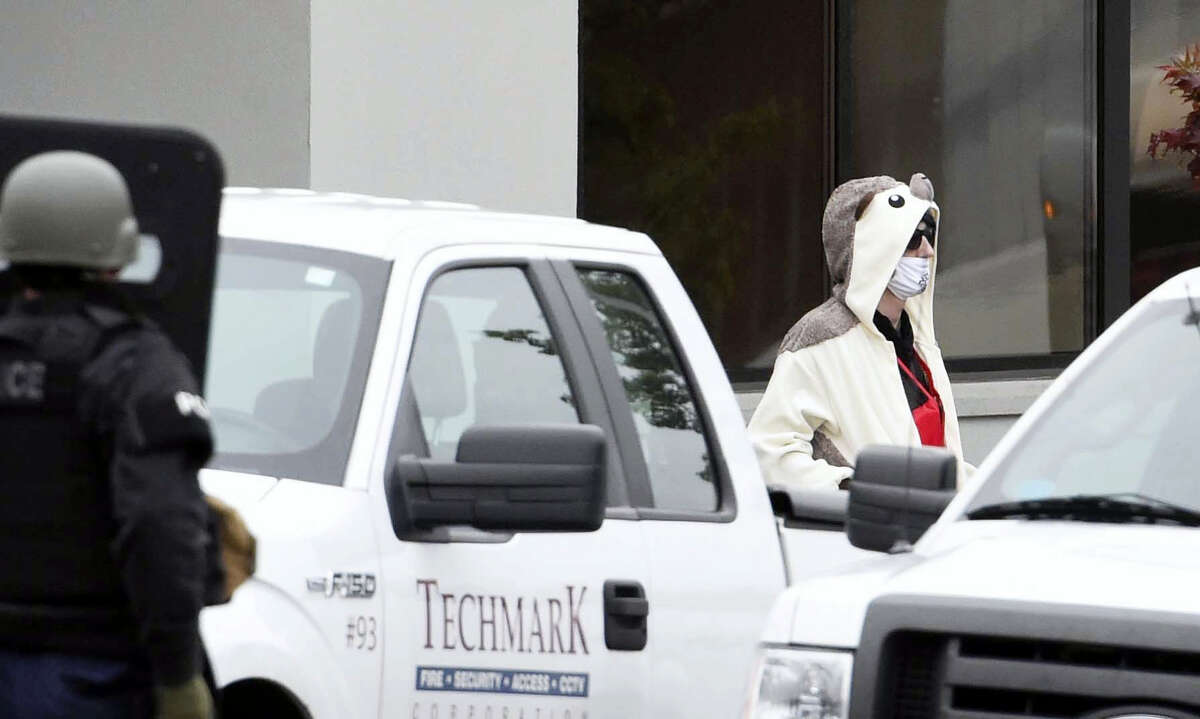 A man wearing a full animal costume and surgical mask walks out of a TV station in Baltimore, Thursday, April 28, 2016. Baltimore police say a department sniper shot the man, who police say walked into a TV station displaying what appeared to be an explosive device on his chest.