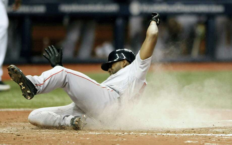 Boston's Jackie Bradley Jr. scores on a two-run double hit by Travis Shaw off Tampa Bay Rays reliever Enny Romero during the seventh inning Tuesday. Photo: STEVE NESIUS — THE ASSOCIATED PRESS  / FR69810 AP