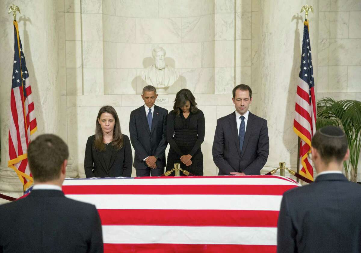 President Barack Obama and first lady Michelle Obama pause as they pay respects beside the casket of Associated Justice Antonin Scalia as it lies in the Great Hall of the Supreme Court, in Washington, Friday, Feb. 19, 2016. The funeral is taking place Saturday morning at the National Shrine of the Immaculate Conception.