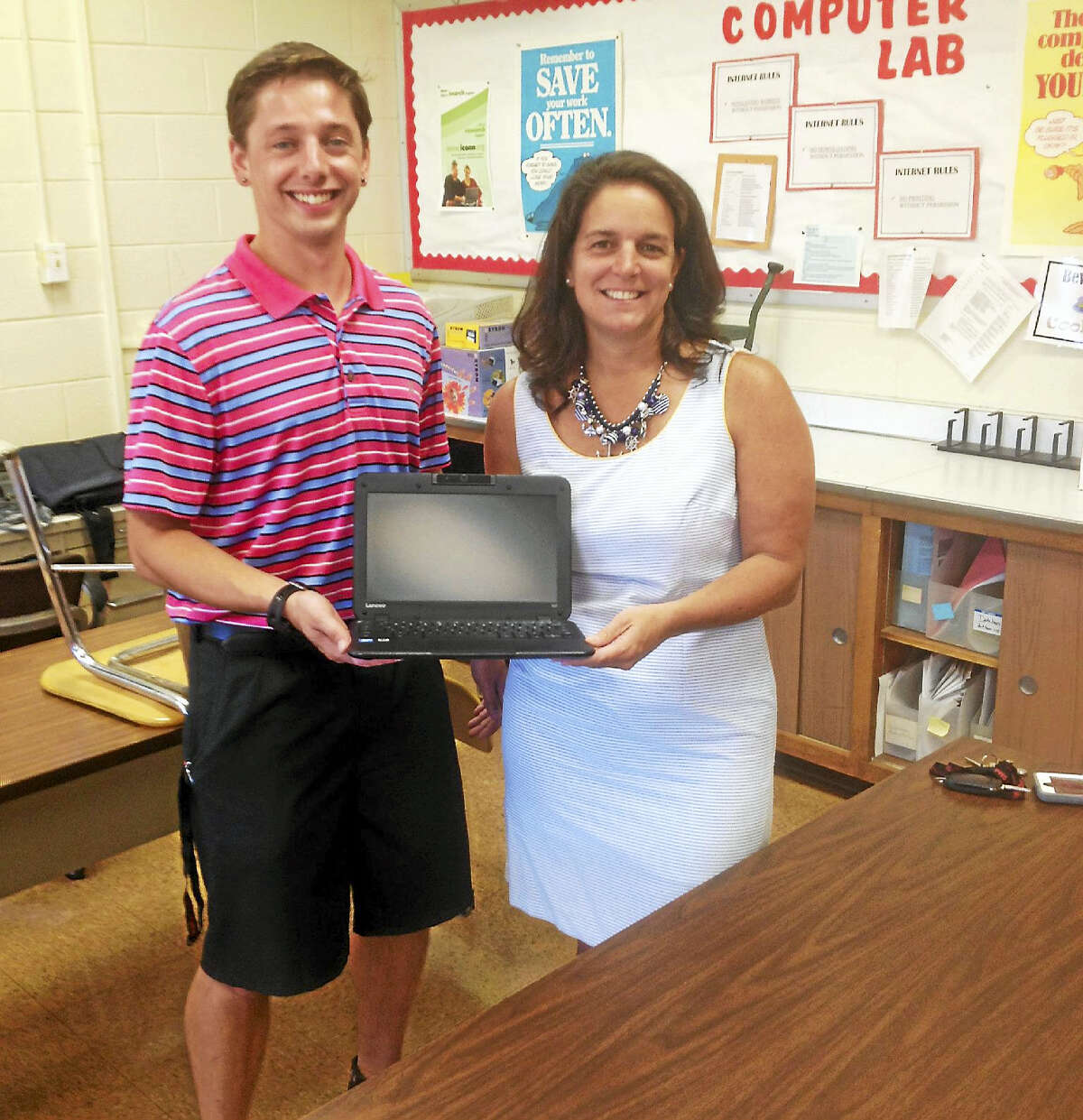 Portland Public School Technology Integration Specialist Michael Peck and Director of Curriculum and Technology Krista Karch show off the new Lenovo notebooks that will be given out to all district fifth- through 12-graders come mid-September.