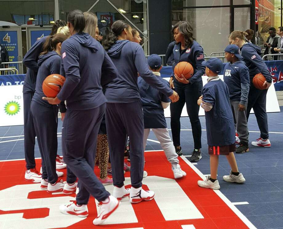 First lady Michelle Obama, fourth from right, joins members of Team USA and some children on a makeshift basketball court erected on New York City's Times Square, Wednesday. The first lady was on hand as the United States Olympic Committee marked 100 days until the beginning of the 2016 Summer Olympics in Rio de Janiero. Photo: The Associated Press  / Copyright 2016 The Associated Press. All rights reserved. This material may not be published, broadcast, rewritten or redistributed without permission.