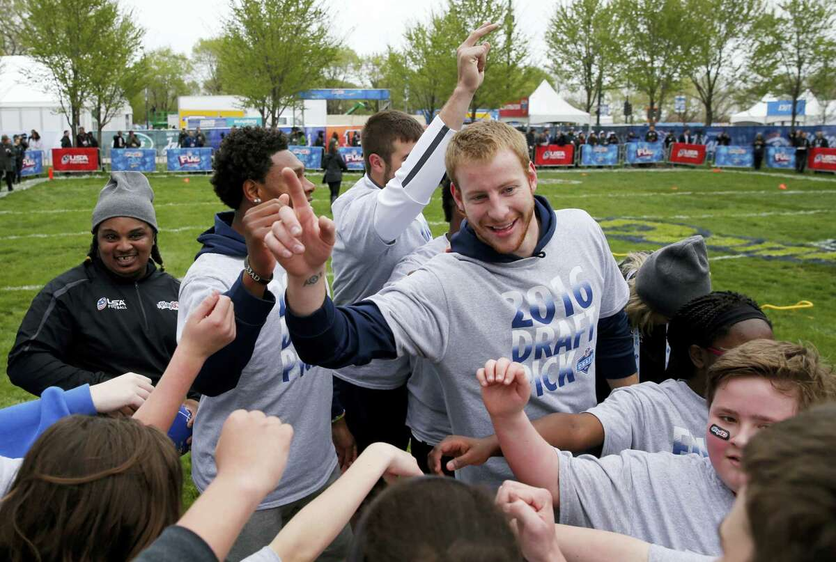 North Dakota State's Carson Wentz huddles with children during an NFL Play 60 event at Grant Park Wednesday in Chicago before today's first round of the NFL football draft.